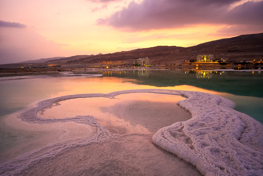 Salt formations on the Dead Sea after Sunset. In the background the Ein Bokek Resorts.