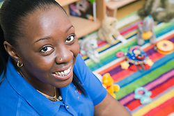 Nursery nurse; at work in mobile creche; smiling,
