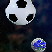 Studio shot of a black and white soccer ball as the moon in line with the planet earth and against a space background.