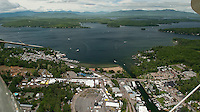 As the clouds clear on Saturday a steady flow of traffic begins to arrive for the beginning of Laconia's Motorcycle Week as seen from Lakes Biplane looking down on Weirs Boulevard and Lake Winnipesaukee.  (Karen Bobotas/for the Laconia Daily Sun)