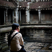 Young woman sitting quietly in Angkor Wat (Siem Reap, Cambodia - Oct. 2008) (Image ID: 081024-0749561a)