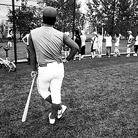 BEIJING, JULY -18: a member  of the Chinese  baseball team looks on as school kids admire the players at practise.