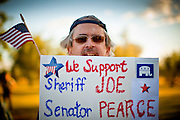 19 MAY 2011 - PHOENIX, AZ: David Mahan, (CQ) from Tempe, hold up a sign supporting Sheriff Joe Arpaio and Russell Pearce in Paradise Valley Park in Phoenix Thursday evening. About 100 people attended the rally, which was to support some of the state's most conservative politicians including Joe Arpaio, Russell Pearce and John Kavanagh. The rally was sponsored by the Maricopa County Republican Party and a Tea Party group.     PHOTO BY JACK KURTZ