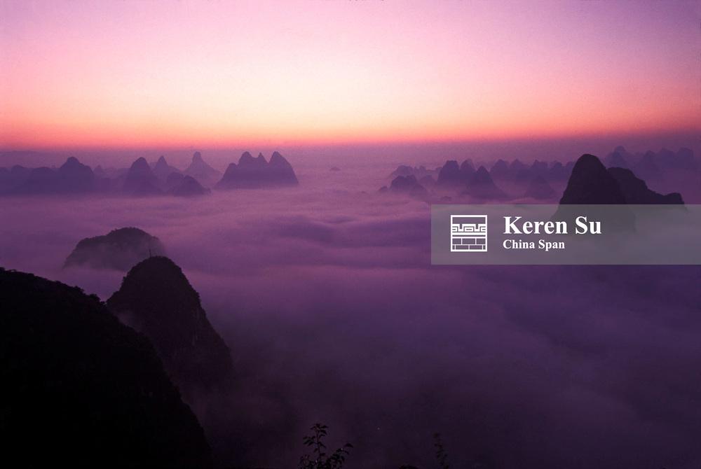 Karst hills above clouds at sunrise, Yangshuo, Li River area, Guangxi Province, China