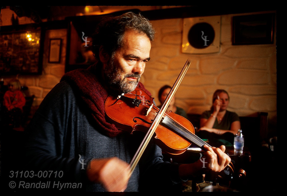 Fiddler Mike Venner performs during a pub session at Barr Na Sraide in town of Dingle, Ireland.