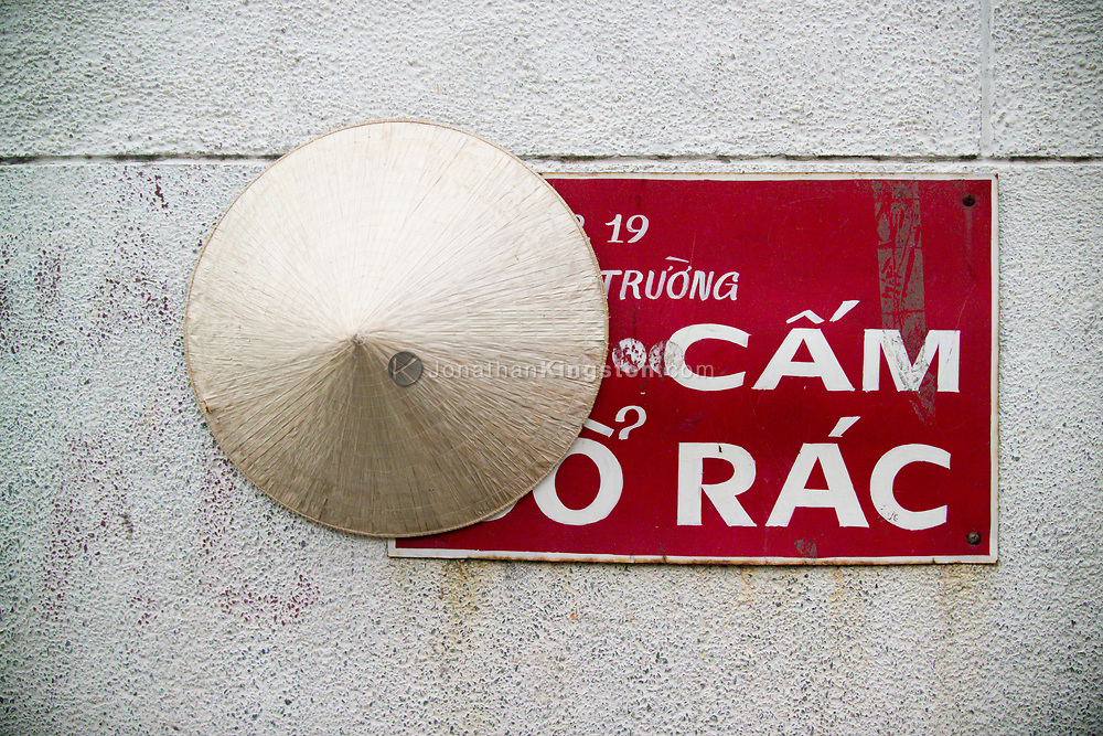 "A sign that reads ""Do not hang anything on this wall"" in Vietnamese is used as a hat hanger, Ho Chi Minh city, Vietnam."