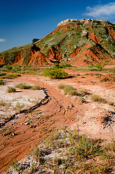 Cathedral Mountain, a butte in Gloss Mountain State Park, rises above an unnamed dry creek bed. The park near Fairview, in northwest Oklahoma, is located in the Gloss Mountains (sometimes referred to as the Glass Mountains) which sparkle in sunlight because the are rich in selenite crystals, a form of the mineral, gypsum. Gypsum leaching out of the ground can be seen in the white ring around the top of Cathedral Mountain. This ring is most visible when the ground is damp. The state park, open from sunrise to sunset offers hiking trails and picnic areas. There is no camping.