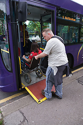 Young woman with Cerebral Palsy in a wheelchair and her boyfriend off a bus using a  mobility ramp,