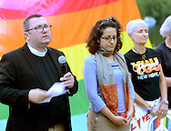 From left, Rev. Michael Ruk reads names of victims as Rabbi Diana Miller and Geri Delevich listen during a candlelight vigil in support of the victims of the Orlando massacre Monday, June 13, 2016 in New Hope, Pennsylvania.   (Photo by William Thomas Cain)