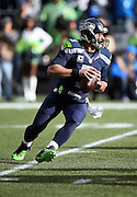 Seattle Seahawks quarterback Russell Wilson (3) scrambles and throws a second quarter interception, his second pick of the day, during the NFL week 20 NFC Championship football game against the Green Bay Packers on Sunday, Jan. 18, 2015 in Seattle. The Seahawks won the game 28-22 in overtime. ©Paul Anthony Spinelli