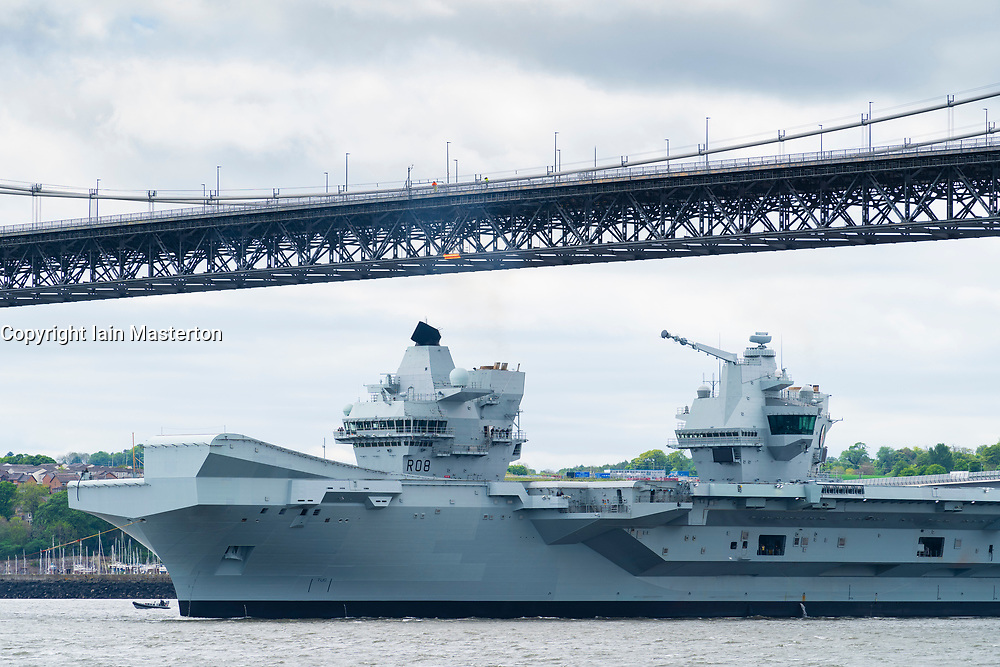 North Queensferry, Scotland, UK. 23 May 2019. Aircraft carrier HMS Queen Elizabeth sails from Rosyth in the River Forth after a visit to her home port for a refit. She returns to sea for Westlant 19 deployment and designed to focus on the operations of her F-35 fighter aircraft. Pictured; Carrier passes underneath the Forth Road Bridge Bridge at low tide.