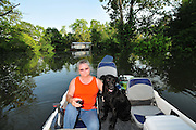 "8/11/11} Vicksburg} -- Vicksburg, MS, U.S.A. -- Patricia Clark is despondent and worried and her dog ""babygirl "" tries to comfort her as she leaves behind her home , pictured in background, that the Mississippi River will FloodMark Bridges,56, thrift store owner, and his dog ""baby girl"" and his girlfriend of 12 years Patricia Clark, a homeDepot garden employee, cruise down Chicksaw Rd in a bass boat in North Kings Community in Vicksburg Mississippi Wed. May 5th 2011. This is the firs time for Patricia to try and remove things from her trailer, that is built on 9ft stilts  AND THE WATER IS CURRENTLY AT 15 ft. and rising and is less than 12 inches from being flooded. Mark and Patricia have lived their all their lives and will return when the Mississippi River recedes,. ark has been helping his neighbors get their belongings to safety. Vicksburg a riverfront town steeped in war and sacrifice, gets set to battle an age-old companion: the Mississippi River. The city that fell to Ulysses S. Grant and the Union Army after a painful siege in 1863 is marshalling a modern flood-control arsenal to keep the swollen Mississippi from overwhelming its defenses. PHOTO©SUZIALTMAN.COM.Photo by Suzi Altman, Freelance."
