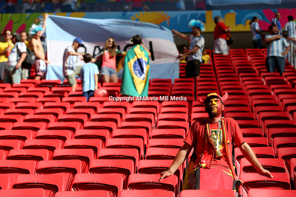 A dejected fan of Belgium with a replica world cup trophy sits at the end of the match in which Belgium got knocked out of the FIFA World Cup