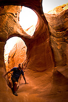 A young man explores Peek-A-Boo slot canyon in the Grand Staircase-Escalante National Monument, Utah.