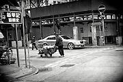 Hong Kong | HongKong | 02.12.2012 :  <br /> <br /> hier: Mann mit Handwagen vor Luxuslimousine<br />   <br /> Sascha Rheker<br /> 20121202<br /> <br /> <br /> <br /> [Inhaltsveraendernde Manipulation des Fotos nur nach ausdruecklicher Genehmigung des Fotografen. Vereinbarungen ueber Abtretung von Persoenlichkeitsrechten/Model Release der abgebildeten Person/Personen liegt/liegen nicht vor.] [No Model Release | No Property Release]