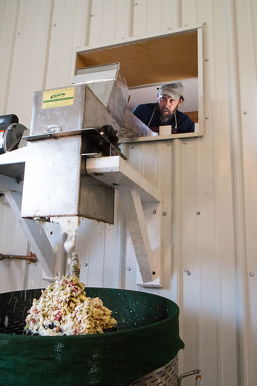 Steven Gougeon adds apples from their orchard into the cider press.