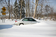 An abandoned car was partially buried in a roadside ditch in Lancaster, New York, USA on Wednesday, November 19, 2014. Up to six feet of snow fell on the region Tuesday, stranding dozens of motorists on roadways and causing at least six deaths.