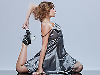 beautiful young caucasian woman girl evening dress supple stretching on studio isolated plain background