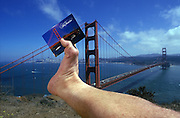 Footograph: Photograph of my right foot holding a postcard of the Golden Gate Bridge at the Golden Gate Bridge with San Francisco in the background.