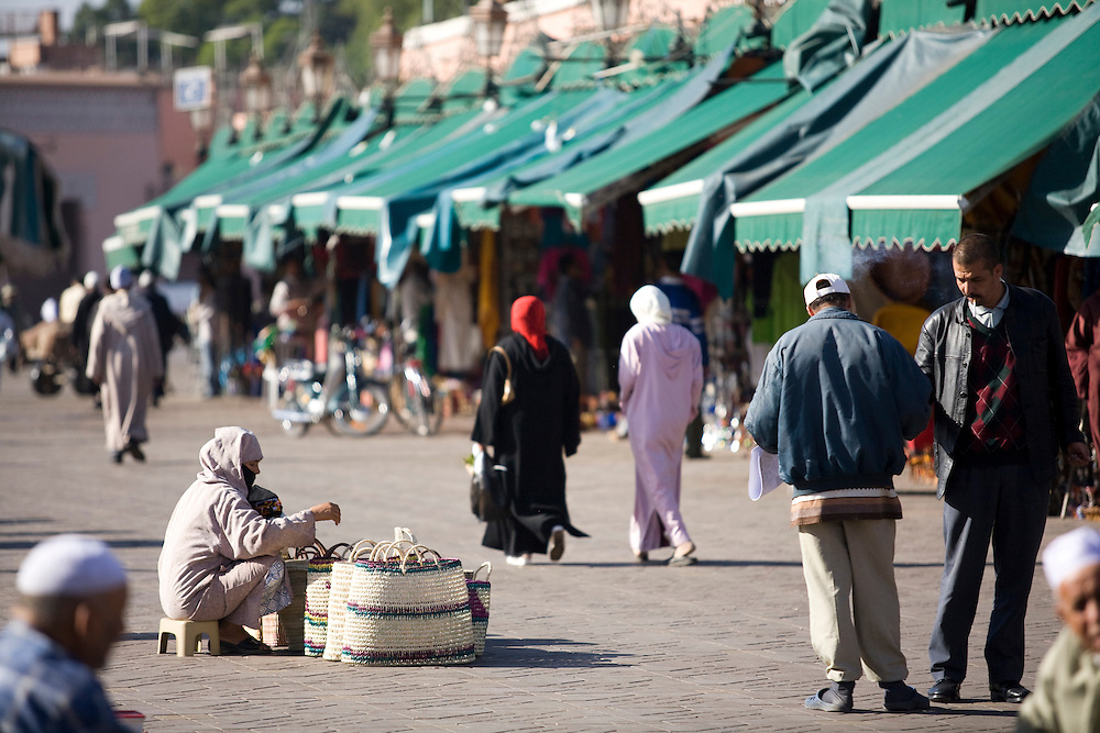 A woman sells her wares to passer-bys in the morning. Djemaa el Fna is the old center square an market in Marrakech.
