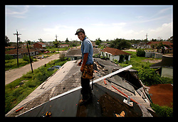 29 August 2006 - New Orleans - Louisiana. Lower 9th ward. On the one year anniversary of hurricane Katrina, and most of the area remains derelict and abandoned. However a crew of undocumented Honduran immigrants work in the mid day heat to repair a roof, overlooking the devastation all around them. A small symbol of hope amidst the rubble.