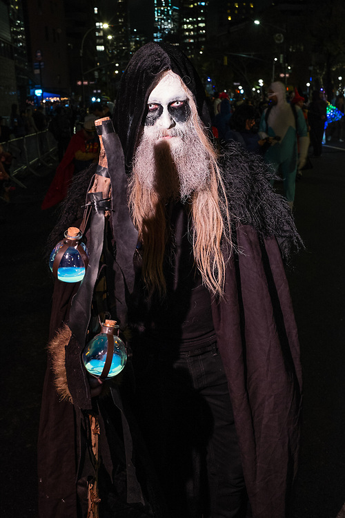 New York, NY - 31 October 2019. the annual Greenwich Village Halloween Parade along Manhattan's 6th Avenue. A beared wizard with his staff and bottles of potions.