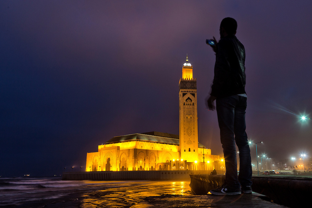 Casablanca, Morocco. Each evening, both young and old stroll the grounds and the sea wall of the Hassan II mosque in Casablanca-taking in the intricacies of the architecture while watching the sun set, and waves pound the supporting rocks.  They come out each evening to enjoy the scene as the lights of the mosque come on when the sun sinks into the horizon, making pictures with their phones. The Hassan II mosque is the largest mosque in Morocco, and the seventh largest in the world. Beautifully designed by a French architect, the mosque towers above the Atlantic coast, and is the most prominent structure in the city of Casablanca.