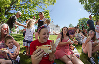 Brooke Demers-Polland enjoys a hot dog with family and friends on the lawn following Gilmanton's 4th of July parade Tuesday morning.  (Karen Bobotas/for the Laconia Daily Sun)