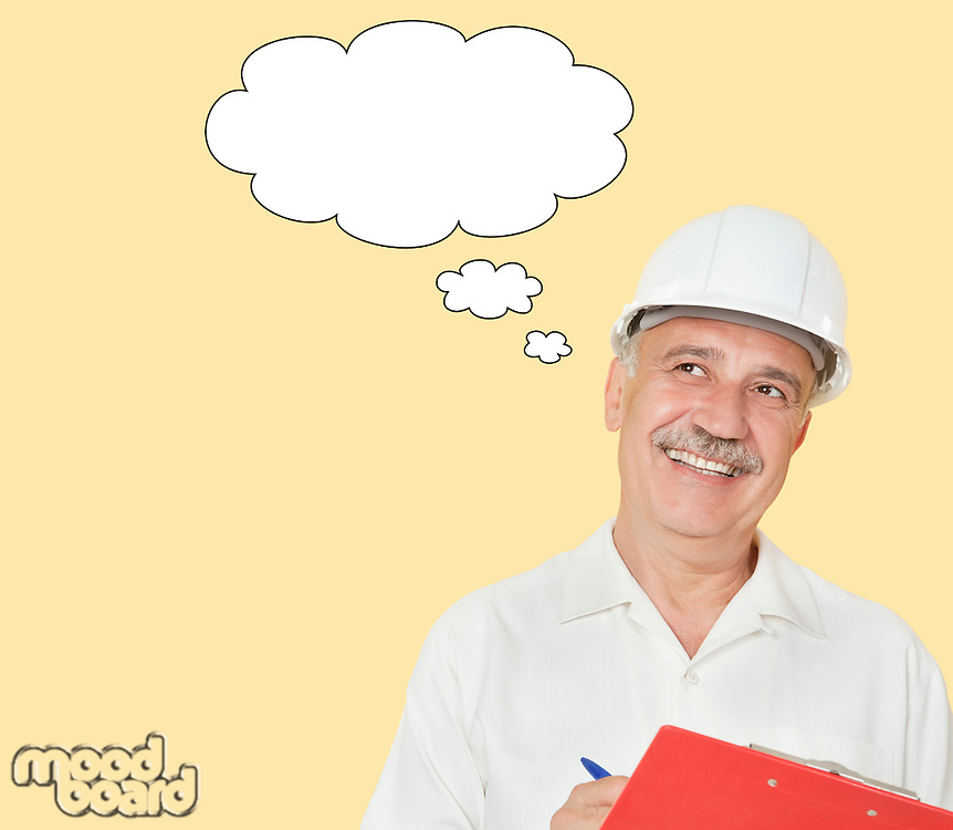 Senior constructor with clipboard and speech bubble looking away over yellow background