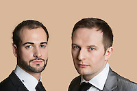 Portrait of young businessmen over colored background