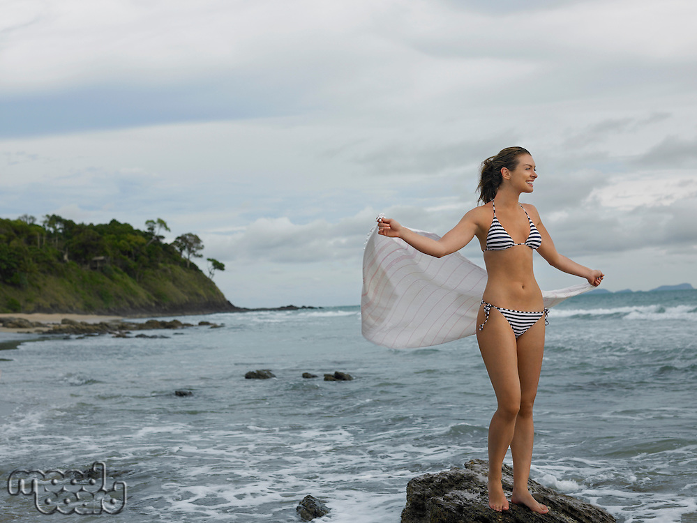 Young Woman Standing on Rock at Beach