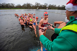 © Licensed to London News Pictures. 25/12/2016. London, UK. Swimmers receive a a drink called Nelsons Blood (champagne and tawny port) as they leave the water. Members of the Serpentine Swimming Club brave the cold waters at the Serpentine Lake in Hyde Park, London to compete for the traditional Peter Pan Cup on Christmas Day, December 25, 2016. Photo credit: Ben Cawthra/LNP