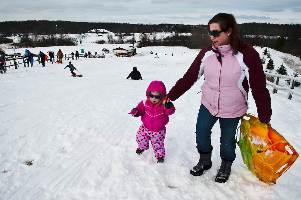 Lathan Goumas | The Flint Journal..January 14, 2012 - Erin Hibbard helps her two-year old daughter, Olivia Hibbard, walk up a sledding hill at Creasey Bicentennial Park in Grand Blanc Township on Saturday.