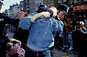 A man in a denim jacket in a head lock being arrested at a demonstration, UK, 2000's