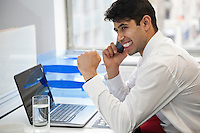 Excited businessman using cell phone at office desk