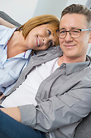 Portrait of smiling man sitting with woman at home