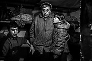 Zarina, 9, (right) is standing next to her grandmother, Tamara, and her brother Valiera, 18, in the small bomb shelter that the family regularly uses during heavy fighting, in the town of Zaitsevo, near the frontline in eastern Ukraine.