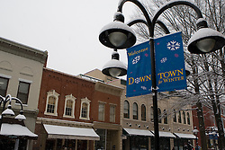 "A light pole with signs that read ""Welcome Downtown for Winter"", during a snow storm, Charlottesville, Virginia on January 18, 2008."