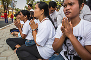 "01 FEBRUARY 2013 - PHNOM PENH, CAMBODIA: A mourner wearing a tee shirt with the photo of former King Norodom Sihanouk on it, prays as the King's funeral procession passes her in Phnom Penh. Norodom Sihanouk (31 October 1922 - 15 October 2012) was the King of Cambodia from 1941 to 1955 and again from 1993 to 2004. He was the effective ruler of Cambodia from 1953 to 1970. After his second abdication in 2004, he was given the honorific of ""The King-Father of Cambodia."" Sihanouk died in Beijing, China, where he was receiving medical care, on Oct. 15, 2012. His cremation is will be on Feb. 4, 2013. Over a million people are expected to attend the service.     PHOTO BY JACK KURTZ"
