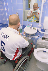 Young man; who is a wheelchair user; washing his face in purposebuilt bathroom in bedsit at direct access hostel for homeless and vulnerably housed young people,