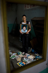 Zhao Xiao Ying, 36, holding a picture of her son Ji Qing Zhen, 12, is seen at Fuxin No.2 Primary  School in Wufu, Sichuan province May 25, 2008.