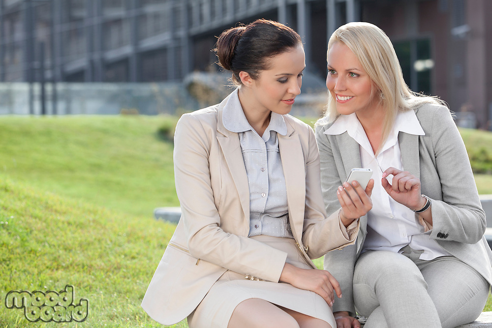 Young businesswomen with mobile phone sitting against office building