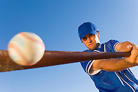 Baseball player hitting ball with bat (low angle view)