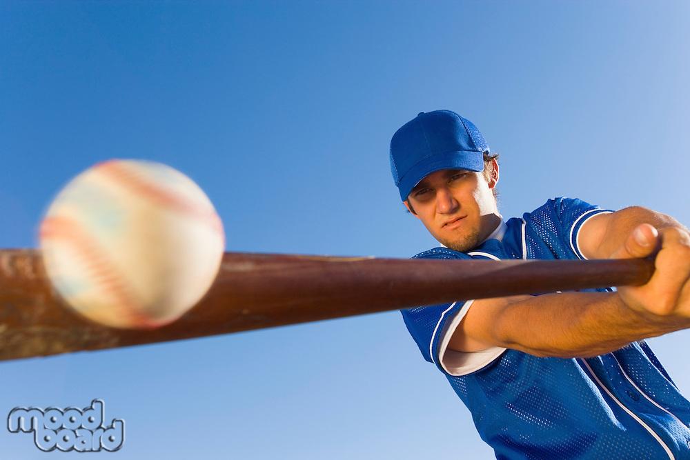 Baseball player hitting ball with bat (low angle view)