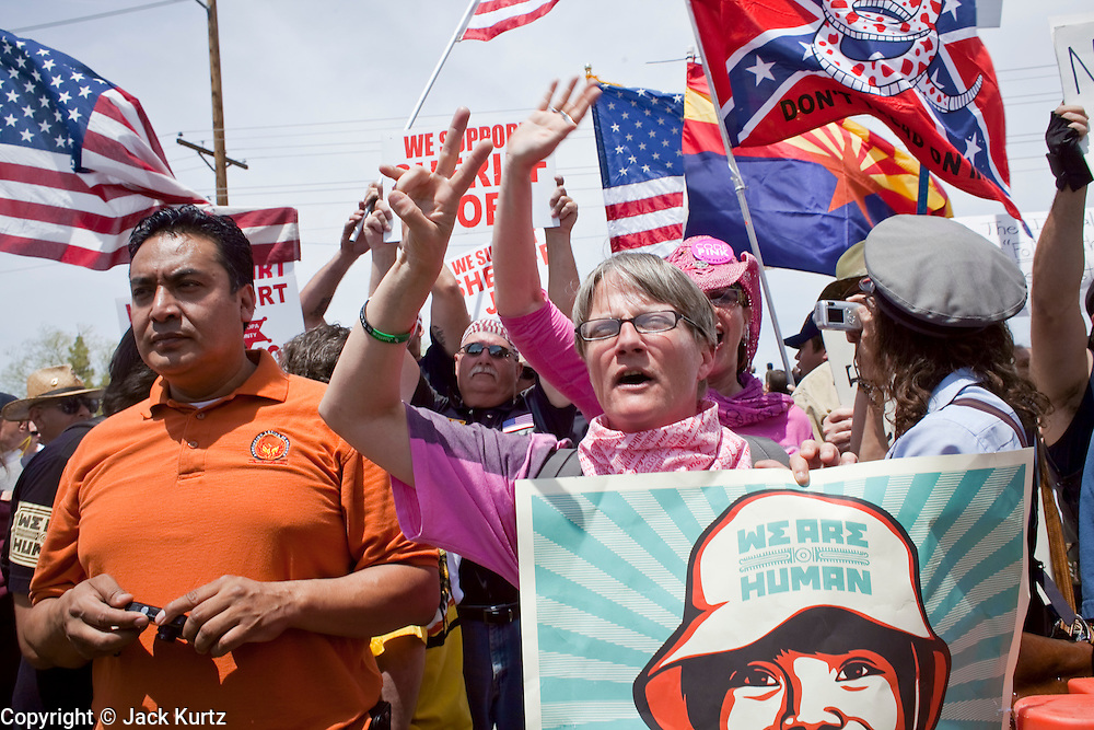 02 MAY 2009 -- PHOENIX, AZ: Liz Hourican (CQ center pink shirt) an opponent of Sheriff Joe Arpaio from Code Pink stands amidst a group of Arpaio supporters and shouts at the sheriff Saturday. Hourican's shouting forced the sheriff to move the location of his press conference. About 1,500 people opposed to Sheriff Joe Arpaio's treatment of prisoners and his high profile crime suppression anti-undocumented raids, marched from his office to downtown Phoenix to the jail complexes on Durango in south Phoenix Saturday. Photo by Jack Kurtz
