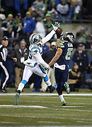 Seattle Seahawks wide receiver Jermaine Kearse (15) catches a 63 yard touchdown pass for a 14-7 second quarter Seahawks lead while covered by Carolina Panthers cornerback Bene' Benwikere (25) who leaps in the air and tries to break up the pass during the NFL week 19 NFC Divisional Playoff football game against the Carolina Panthers on Saturday, Jan. 10, 2015 in Seattle. The Seahawks won the game 31-17. ©Paul Anthony Spinelli