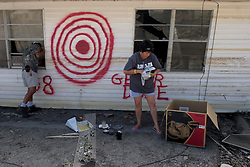 04 Oct, 2005.  New Orleans, Louisiana. Hurricane Katrina aftermath.<br /> Chris Kopp collects all he can from his sister Sara Fullagar's smashed home in the Arabi neighbourhood. Chris' brother in law had painted a large target on the outside of the house which now rests in the middle of the street with the Louisiana words 'Get'er done,' a reference to the bulldozers to go ahead and destroy what remains of the house.<br /> Photo; ©Charlie Varley/varleypix.com