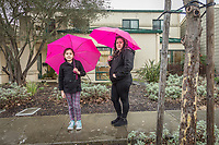 Brenda Chairez with her daughter, Briseida, pause on Washington Street during a rain storm  in Calistoga