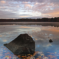Lake Cochituate borders the Boston suburbs Natick, Wayland and Framingham and is part of the Cochituate State Park in Massachusetts. This peaceful fall foliage photography image was captured on a quiet morning at the end of autumn season - katahum. The early morning light painted the New England scenery in beautiful colors and warm hues. A mixture of blue sky and clouds and the bolder surrounded by autumn leaves provided perfect background and foreground elements for this Massachusetts nature photography image. I love experience the quietude that comes with an early morning photo outing. <br /> <br /> Lake Cochituate fall foliage photos are available as museum quality photography prints, canvas prints, acrylic prints or metal prints. Prints may be framed and matted to the individual liking and room decor needs:<br /> <br /> http://juergen-roth.pixels.com/featured/lake-cochituate-juergen-roth.html<br /> <br /> Good light and happy photo making! <br /> <br /> My best, <br /> <br /> Juergen <br /> Image Licensing: http://www.RothGalleries.com <br /> Fine Art Prints: http://fineartamerica.com/profiles/juergen-roth.html <br /> Photo Blog: http://whereintheworldisjuergen.blogspot.com <br /> Twitter: https://twitter.com/naturefineart <br /> Facebook: https://www.facebook.com/naturefineart <br /> Instagram: https://www.instagram.com/rothgalleries