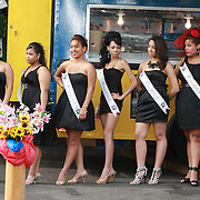 2009, Lawrence, MA. Candidatas al concurso Miss Peinado se preparan a desfilar.<br /> <br /> Esta imagen es interesante por que resume una mezcla de elementos dispares. Lo primero, es que el setting del concurso de belleza es un parking lot. Segundo, el fondo, background del evento es una casilla de venta de chimi-churis y fritura. Lo tercero a reseñar es lo primero que se nota: Las 7 candidatas -todas a exception de una- luce estar en un mundo propio, como si estuvieran cada una sintonizando y oyendo su propia emisora.<br /> <br /> Mientras el fotógrafo justo en frente, hace esfuerzos desesperados en procurar de concentrar la atención de las 7. <br /> <br /> Otro elemento es el ingenioso arreglo floral que cubre la parte alta del poste amarillo de seguridad y como contrasta con las hermosas piernas y calzados detrás. <br /> English: English translation available upon request